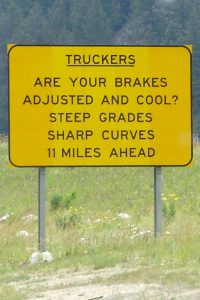 A highway sign warning truckers to check their brakes before starting down a steep grade.
